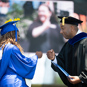 Chancellor fist bumping female student