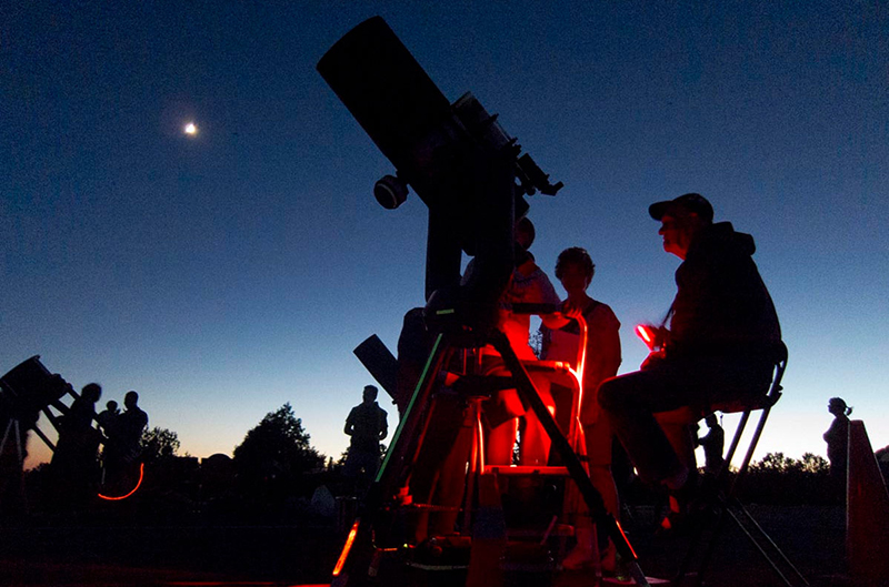 people viewing the moon with telescopes