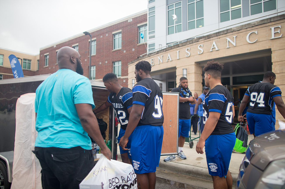 Athletes helps students move in