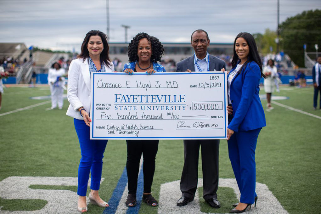 Dr. Clarence Lloyd, second from right, presents Fayetteville State University Interim Chancellor Peggy Valentine, second from left, a check for $500,000. Also pictured from left are Lorna Ricotta, Vice Chancellor for Institutional Advancement, and Jalisha Pone, Associate Director of Development.
