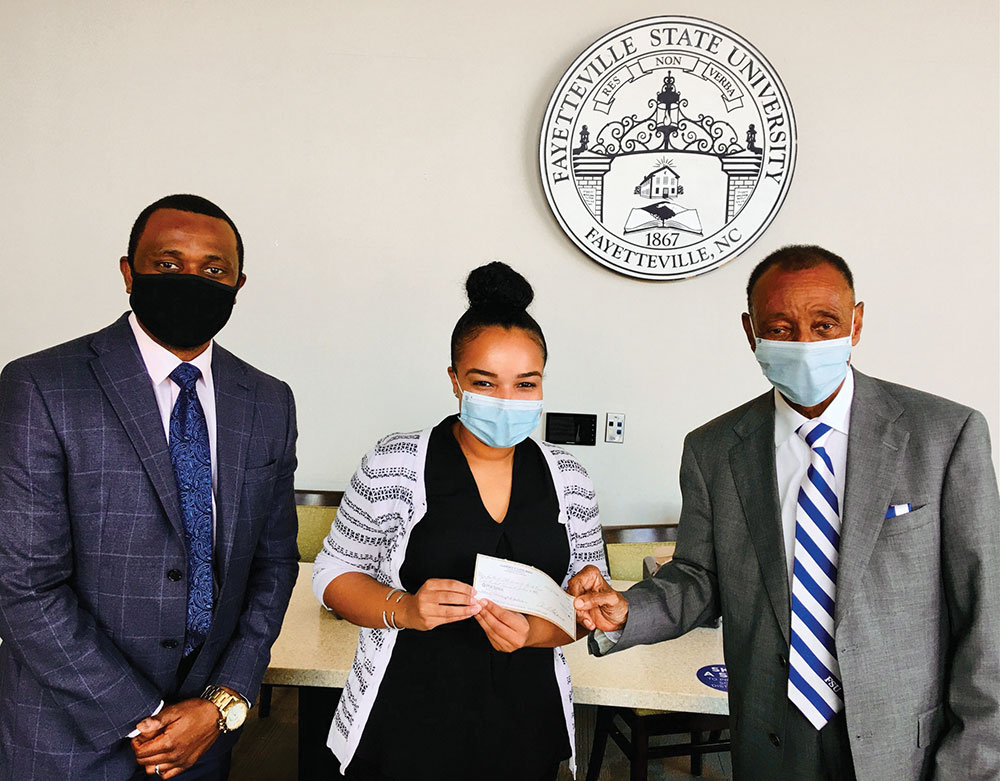 Chris Davis, Associate Vice Chancellor for Development, and Jasmin Sessoms, Interim Director of Alumni Affairs, accept a donation from Dr. Clarence E. Lloyd